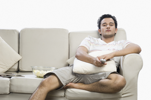 Man lounging on couch watching TV