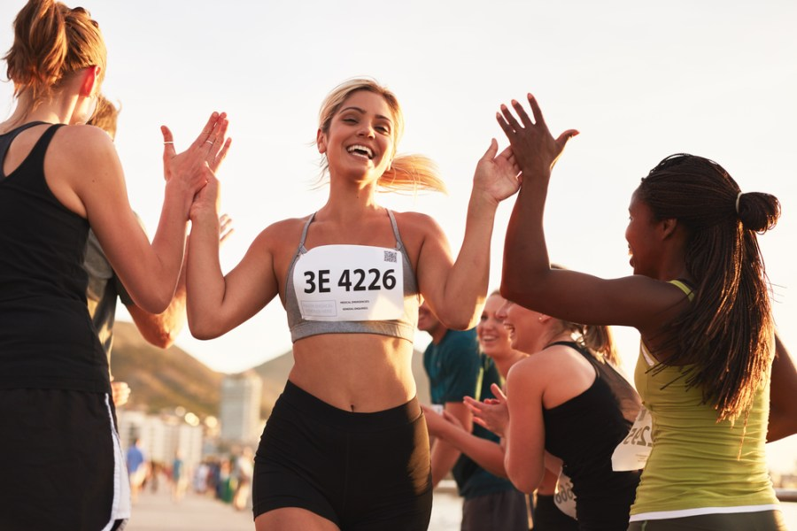 Woman finishing a running race with friends