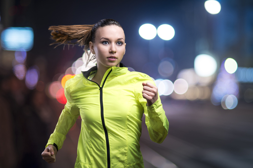 Woman running at night in bright clothing