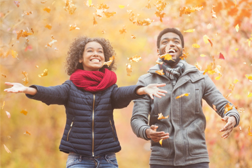 Couple throwing leaves and playing outside