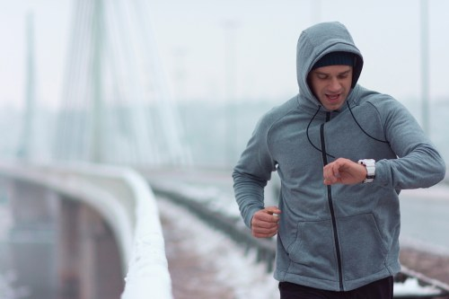 Man running for fitness in the winter checking watch