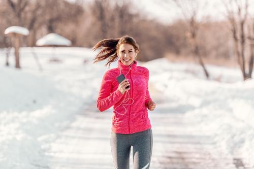 Sporty woman jogging for fitness in the snow