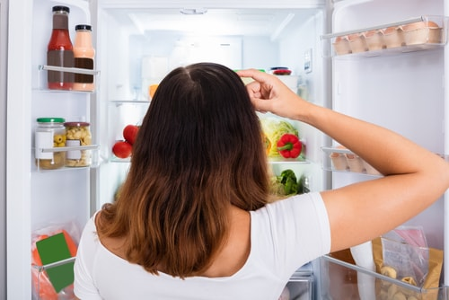 Woman looking at refrigerator deciding what to eat