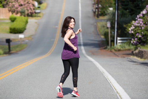 Woman running down a hill for fitness