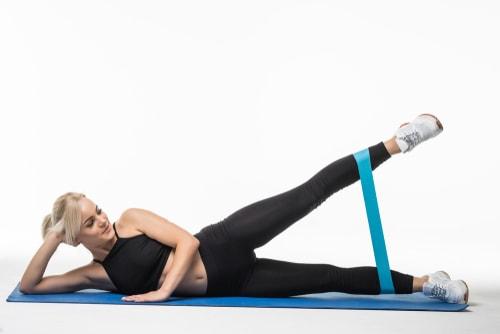 Woman doing side leg raises lying down with band