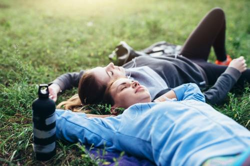 2 athletic women taking a nap in the grass