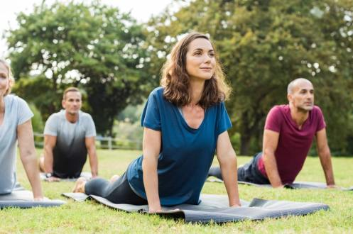 Middle aged adults doing yoga in a park