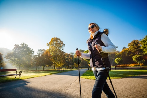 Woman nordic walking in a sunny park