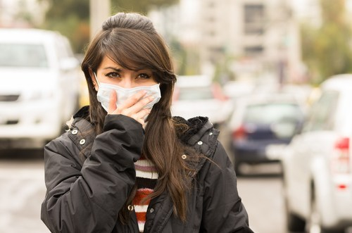 Woman covering mouth with mask because of pollution