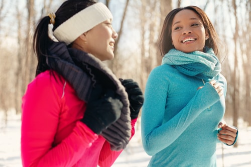 2 women fitness walking together in the snow