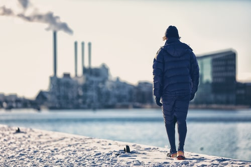 Man walking in front of polluting factory with smoke