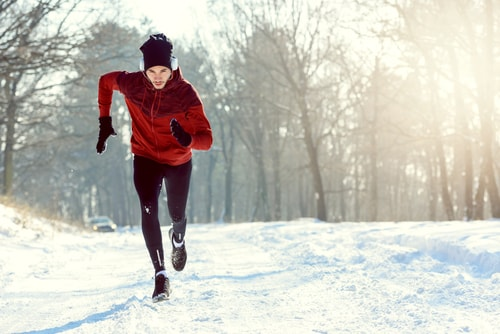 Determined man jogging on a snowy winter road