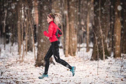 Woman running for fitness on a snowy trail