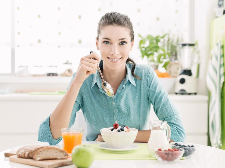 Woman eating healthy delicious breakfast in kitchen