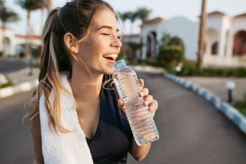 Woman smiling and drinking water during a walk