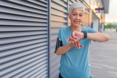 Woman checking fitness watch during walk