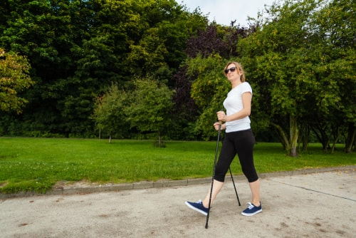 Woman nordic walking in a green park