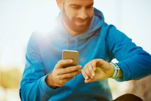 Runner checking phone and smart watch