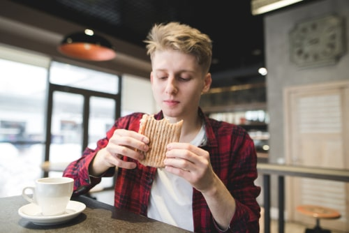 Man drinking coffee and eating sandwich