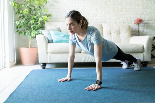 Woman doing strength exercises in living room