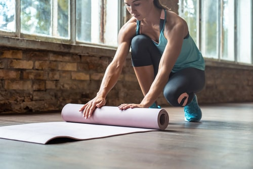 Woman unrolling yoga or pilates mat