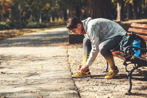 Man tying shoes on park bench during a walk