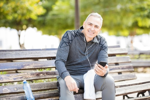 Man checking phone on a park bench
