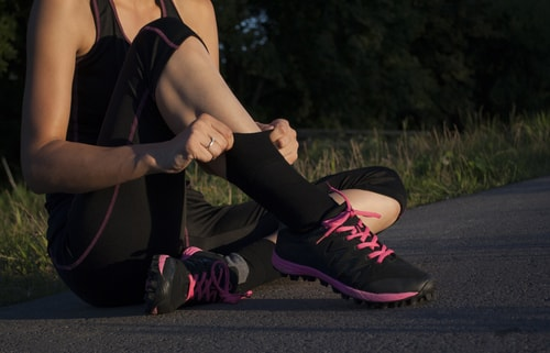 Pulling up socks during a walk or run