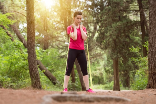 Woman working out in nature with a resistance band