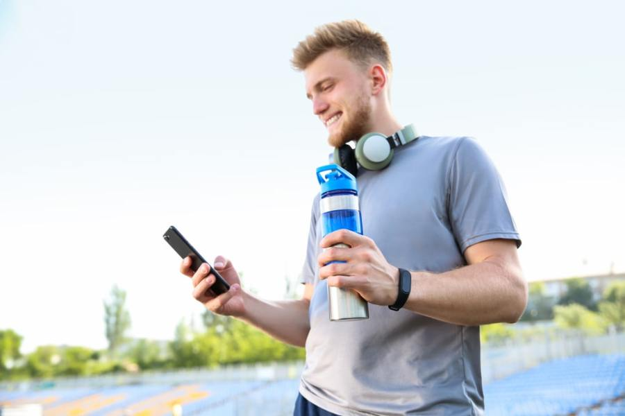 Man with water checking phone during a fitness walk