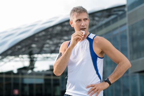 Jogger eating an energy bar in front of buildings
