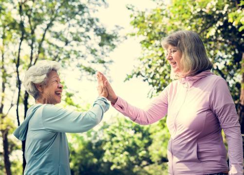 Seniors hi-fiving after a walking workout