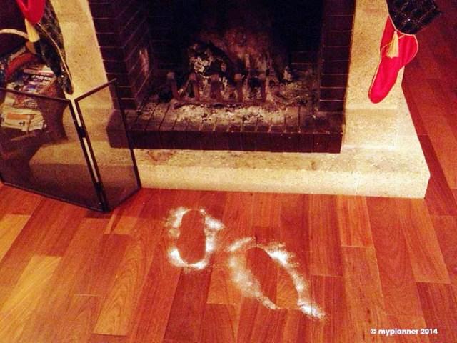 Les bottes enneigées du Père Noël devant la cheminée