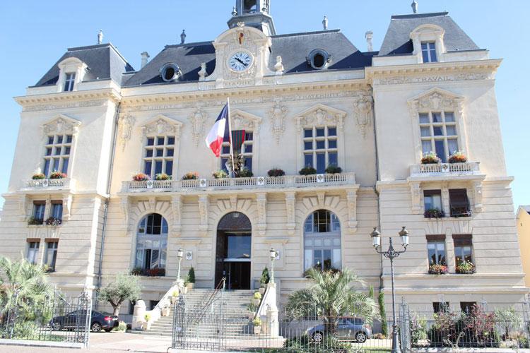 Facade d'une mairie où flotte le drapeau français