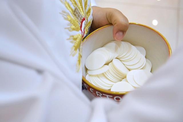 Prêtre tenant un bol d'hostie pour une première communion