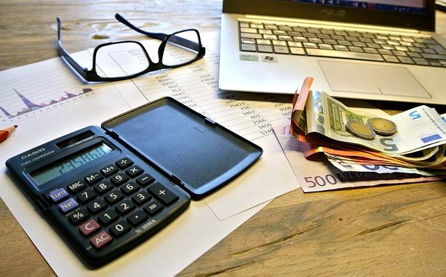 calculatrice monnaie lunettes et ordinateur posés sur un bureau