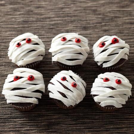 Cupcakes au chocolat en forme de petites momies pour un buffet sucré d'Halloween