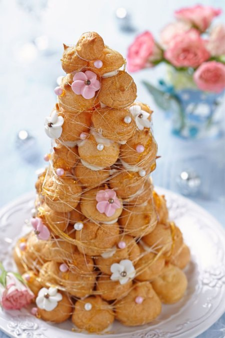 pièce montée de choux décoré de fils de caramel et de fleurs roses en sucre