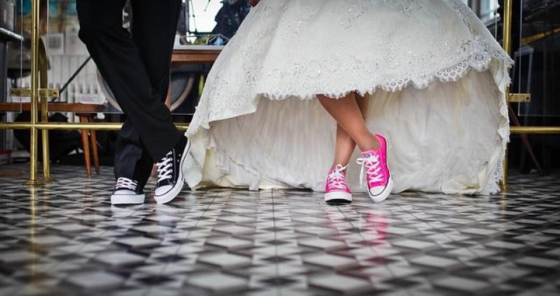 Couple de mariés portant des basquettes converses roses flash et noires