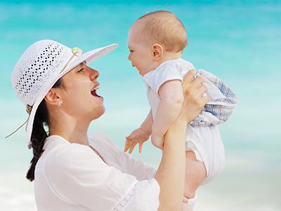 mère souriant à son bébé devant la mer