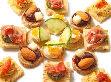petits canapés apéritifs multicolores disposés en étoile sur une assiette blanche