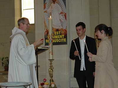 parrain et marraine de baptême tenant un cierge