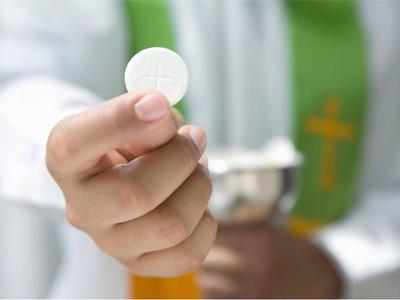 première communion: un prêtre tient un hostie