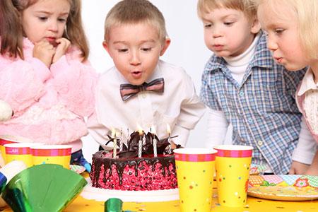 garçon soufflant ses bougies d'anniversaire
