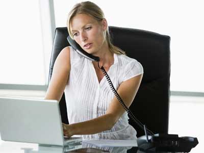 femme blonde au téléphone devant son ordinateur