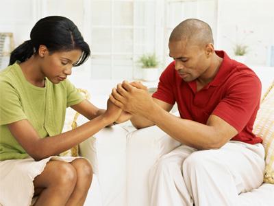 parents joignant leur main pour prier ensemble - la prière des parents du baptême à l'église