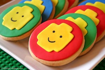 gateau d'anniversaire lego: biscuits lego en pâte à sucre rouges et verts avec une tête de lego jaune au centre