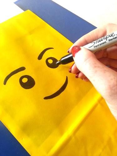 Femme créant une pochette cadeau d'invité en tête de lego jaune