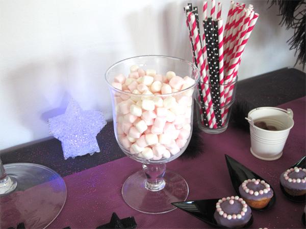 Buffet d'anniversaire Chica Vampiro avec des bonbons et guimauves roses et blanches et des popcakes violets