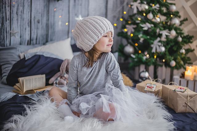 Réveillon de noël 2017: une petite fille s'apprête à déballer ses cadeaux de noël au pied du sapin le matin de Noel